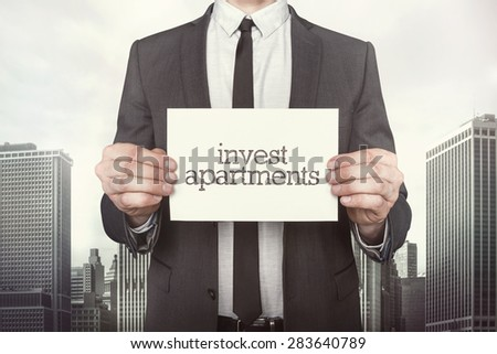 Invest apartments on paper what businessman is holding on cityscape background