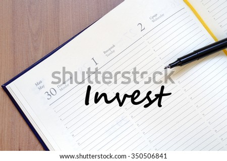 Invest text concept write on notebook with pen