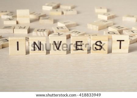 invest word written on wood block. Wooseb Abc - stock photo