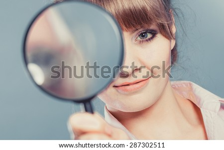 Investigation exploration education concept. Closeup woman holding magnifying glass loupe in hand filtered photo - stock photo