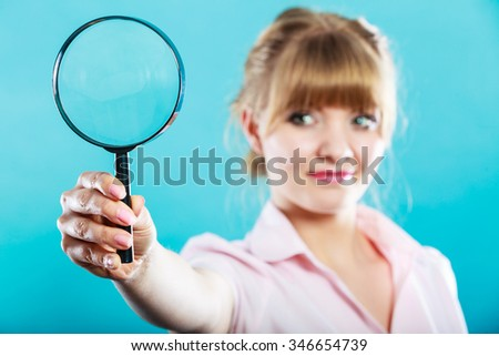 Investigation exploration education concept. Closeup woman holding magnifying glass loupe in hand on blue background - stock photo