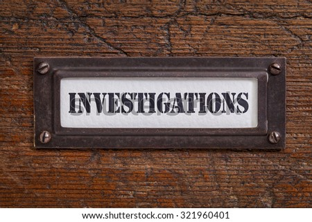 investigations - file cabinet label, bronze holder against grunge and scratched wood