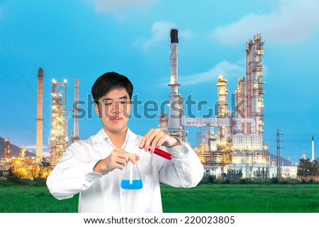 Investigator checking test chemical tubes with chemical factory background - stock photo
