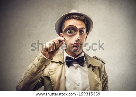 investigator looking with magnifying glass - stock photo