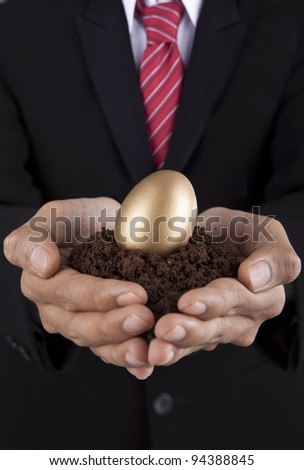 Investment concept businessman holding a golden egg and soil - stock photo