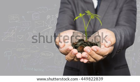 Investment concept, close up of businessman hands holding stack of golden coins with small plant growing out of it - stock photo