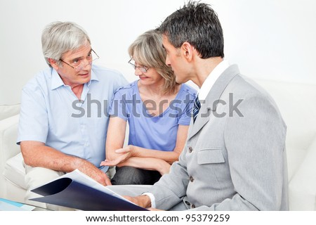 Investment consultant talking to senior couple at home in living room - stock photo