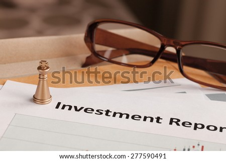 Investment Report letter document and eyeglass; document is mock-up