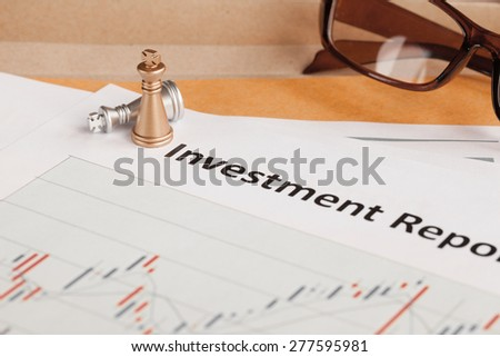 Investment Report letter document and eyeglass; document is mock-up - stock photo