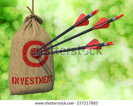 Investment - Three Arrows Hit in Red Target on a Hanging Sack on Natural Bokeh Background. - stock photo