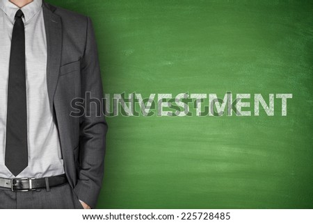 Investment word on green blackboard with businessman - stock photo