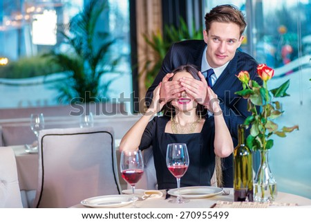 Invisible surprise. Romantic dinner in the restaurant. Young couple sitting at a table in the restaurant until the guy closed the girl her eyes with his hands - stock photo