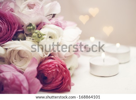 Invitation card. Ranunculus with candles and romantic light - stock photo
