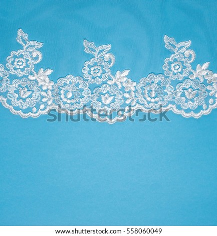 Invitation, greeting or wedding card with white lace on blue background