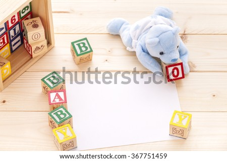 Invitation with blue toy bear spelling the words Baby Boy with wooden a.b.c blocks on pinewood background.