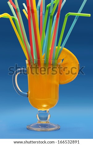 Invite friends to a glass of fresh orange juice with lemon slice and many colorful drinking straws on blue background - stock photo