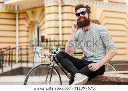 Inviting friend for a ride. Happy young bearded man talking on the mobile phone and smiling while sitting near his bicycle outdoors - stock photo