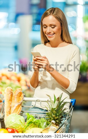 Inviting friends for dinner. Cheerful young woman holding mobile phone and smiling while standing in a food store  - stock photo