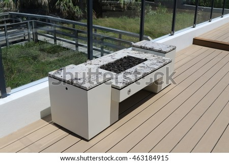 Inviting modern fire pit on an outdoor terrace with glass surrounds.