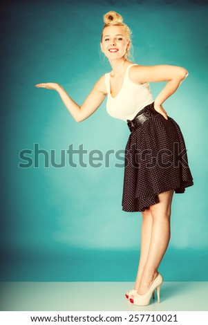 Inviting, showing and sharing concept. Pin up retro girl style. Blonde young full length woman with hand invitation gesture in studio. Vintage photography. - stock photo