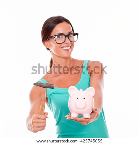 Inviting woman with piggy bank and a hammer while inviting with a toothy smile looking at the camera wearing glasses and a tank top, isolated
