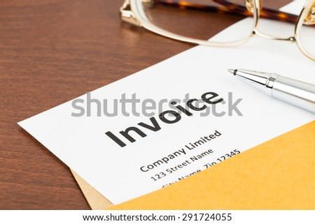 Invoice in envelope with pen, and glasses; document is mock-up