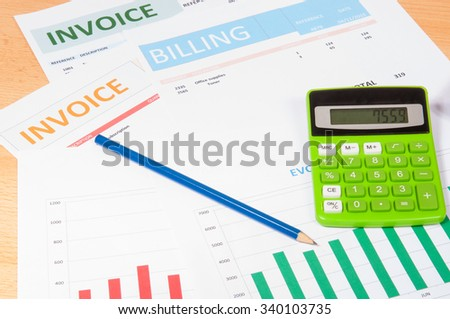 Invoices with a green calculator and a pencil