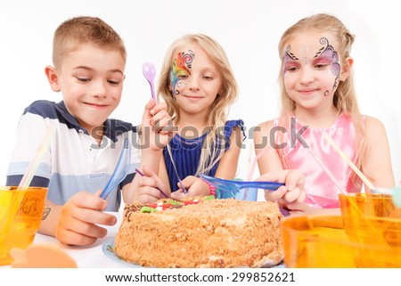 Involved in birthday eating. Nice little children sitting at the table and waiting to taste festive cake. - stock photo