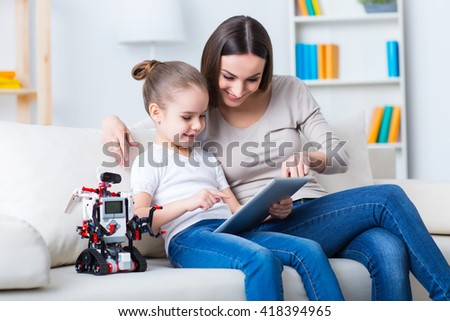 Involved in learning. Positive smiling mother and her daughter sitting on the sofa and using tablet while expressing gladness  - stock photo