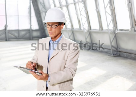Involved in work. Pleasant concentrated handsome architect holding folder and keeping pen while making sketching - stock photo
