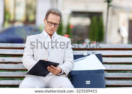 Involved in work. Pleasant serious confident man sitting on the bench and making notes while being busy