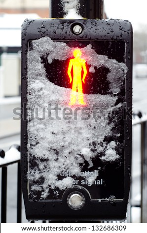 IPSWICH, UK - MARCH 24: Pedestrian crossing (puffin crossing) control covered with snow. Severe weather conditions are causing disruptions in many parts of UK on 24 March 2013. - stock photo