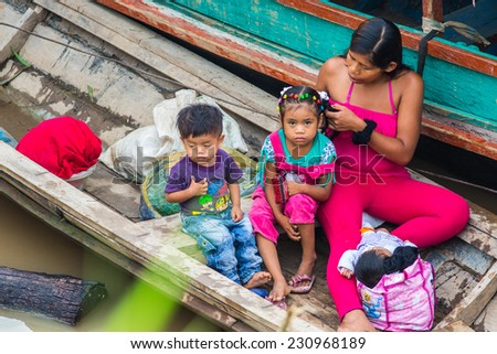 IQUITOS, PERU - CIRCA 2014: A local young woman with her childs on a boat circa 2014, in Iquitos, Peru.