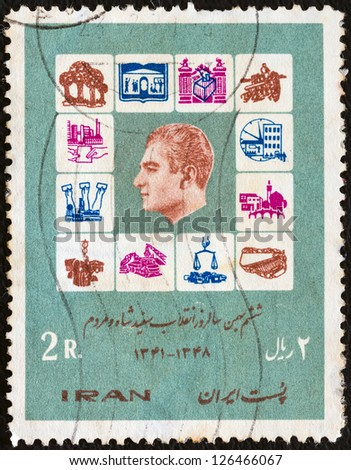 "IRAN - CIRCA 1970: A stamp printed in Iran from the ""Declaration of the Shah's Reform Plan"" issue shows symbols of reform laws and Shah Mohammad Reza Pahlavi, circa 1970."