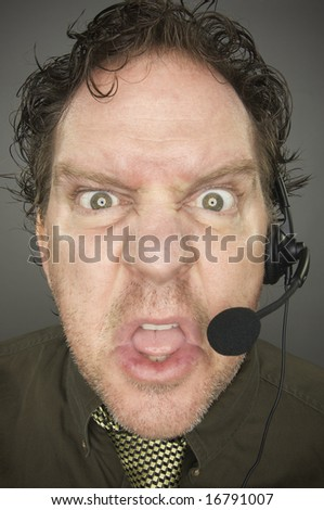 Irate Businessman Wearing a Phone Headset Against a Grey Background. - stock photo