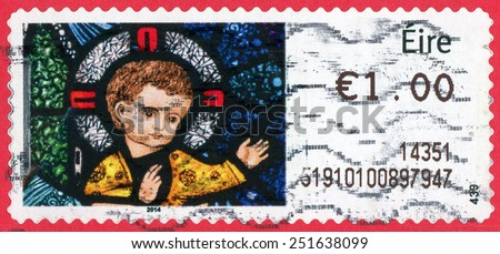 IRELAND - CIRCA 2014: Christmas post stamp printed in IRELAND show infant child Christ at St. Patricks's church Co Mayo; stained glass window by Harry Clarke; '1.00; circa 2014 - stock photo
