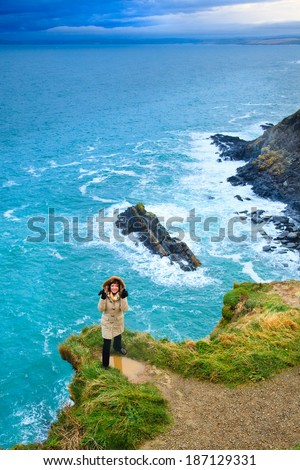 Irish atlantic coast. Woman tourist standing on rock cliff by the ocean Co. Cork Ireland Europe. Beautiful sea landscape natures beauty.