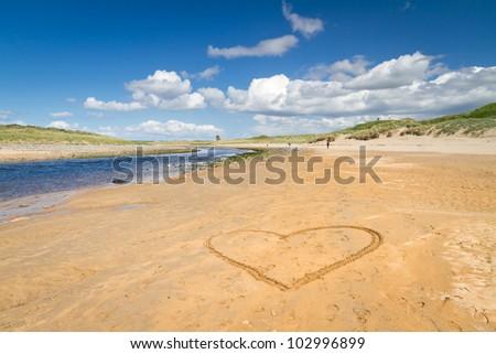 Irish beach with love heart on the sand - stock photo