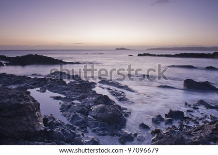 Irish coast line at sunrise. Warm and colorful landscape photograph of a beautiful shore in Ireland, Europe.