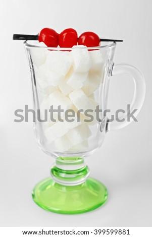 Irish coffee glass with lump sugar and cocktail cherries on grey background - stock photo