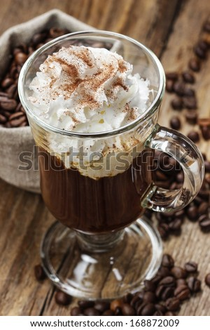 Irish coffee on wooden table among coffee beans - stock photo