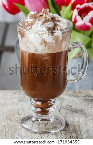 Irish coffee on wooden table. Bouquet of pink and red tulips in the background