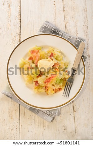 irish colcannon with butter, made with mashed potato, cabbage, grilled bacon and crushes peppercorn, fork on a plate