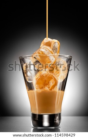 Irish creme liqueur pouring into a glass full of ice. - stock photo