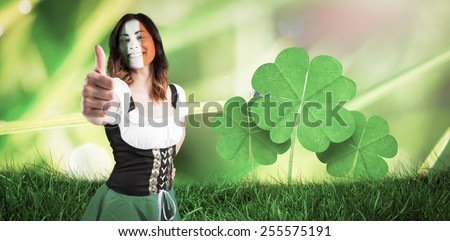 Irish girl showing thumbs up against dew on the grass close up - stock photo