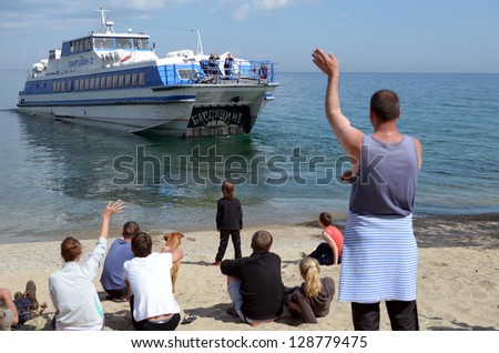 IRKUTSK REGION, LAKE BAIKAL,RUSSIA - JULY,20 2012: People sitting on the beach, waving after the departing ship in July,20 2012, in Irkutsk region, lake Baikal, Russia