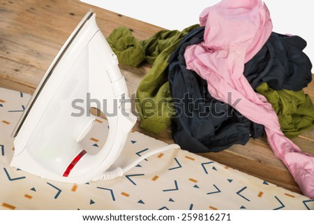 Iron and a big heap of messy, crumpled clothes - stock photo
