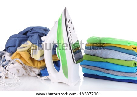 Iron and pile of colorful clothes isolated on white - stock photo