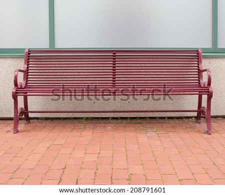 Iron bench against exterior wall with brick foreground. - stock photo