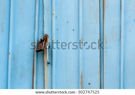 iron blue old gate with a padlock - stock photo